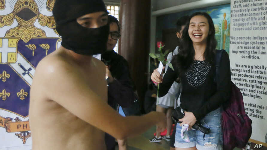 © Student receives rose from protester during naked run to