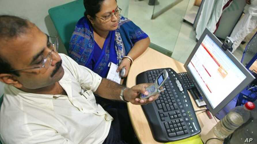A man sends a text message from his mobile phone inside an Internet cafe in the eastern Indian city of Kolkata (file photo)