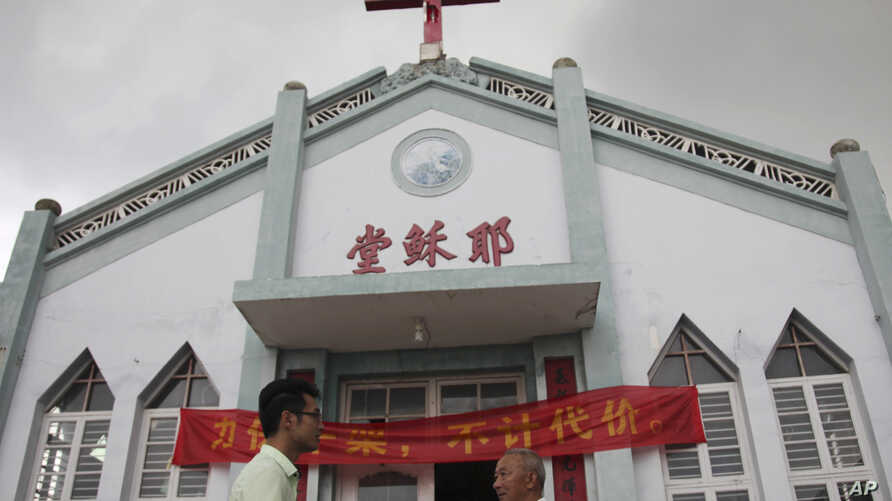 """FILE - In this photo taken July 15, 2014, Pastor Tao Chongyin, left, speaks with church member Fan Liang'an in front of the Wuxi Christian Church with the words """"Church of Jesus"""" in red in Longwan, Wenzhou in eastern China's Zhejiang province."""