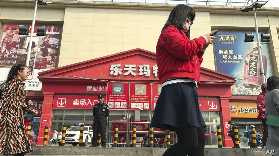 Residents walk past a Lotte Mart where additional security measures are visible in Beijing, China, March 17, 2017. Retail giant Lotte Group, South Korea's No. 5 business group, took the brunt of the backlash after agreeing to let one of its golf cour