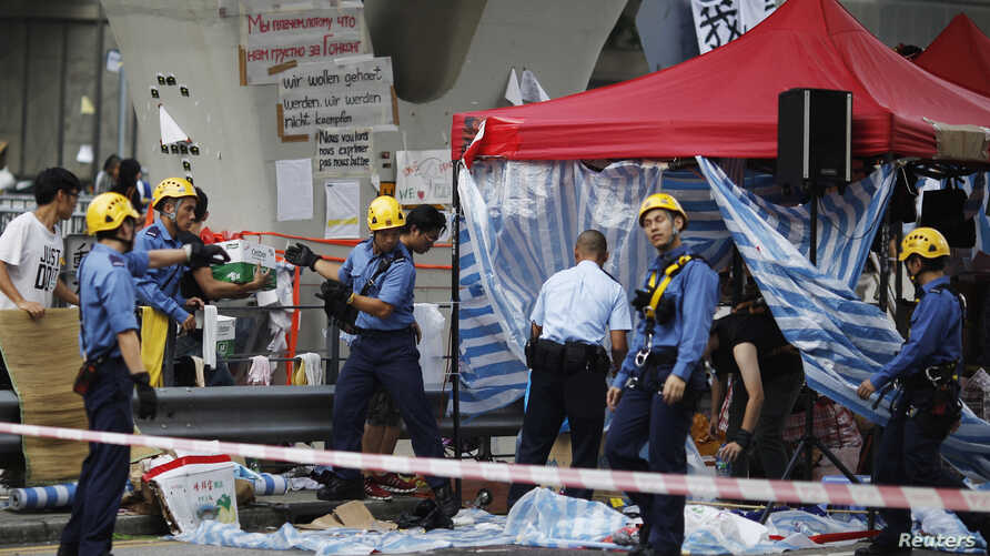 Firefighters remove a tent under a pedestrian bridge as a pro-government supporter threatens to jump off the bridge unless roadblocks set up by Hong Kong pro-democracy protesters are removed in front of the government headquarters in Hong Kong, Oct.