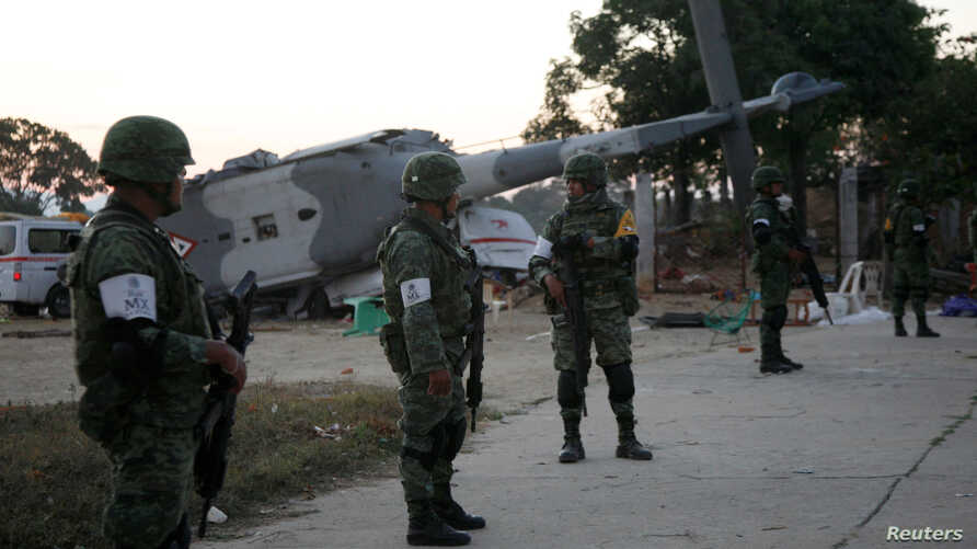 Soldiers stand guard next to a military helicopter that crashed on top of two vans in a field while trying to land in Santiago Jamiltepec, Mexico February 17, 2018.