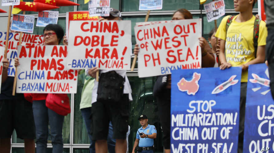 Police guard the entrance to the Chinese Consulate as environmental activists protest the alleged military build-up by China on the disputed group of islands at the South China Sea, Jan. 24, 2017 in the financial district of Makati east of Manila.