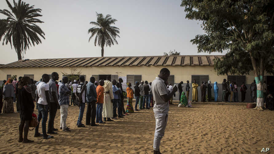 Senegalese voters line up to cast their votes at a polling station in Dakar, Senegal, Sunday Feb. 24, 2019. Voters are choosing whether to give President Macky Sall a second term in office as he faces four challengers.