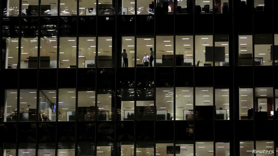 Workers are seen in office windows in the financial district of Canary Wharf in London, Nov. 3, 2015.