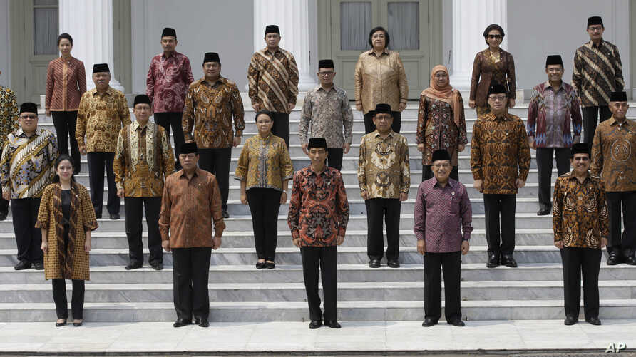 Indonesian President Joko Widodo, front row, center, and his deputy Jusuf Kalla, front row, second right, pose with the newly appointed cabinet ministers after their the inauguration ceremony at the presidential palace in Jakarta, Indonesia, Oct. 27,