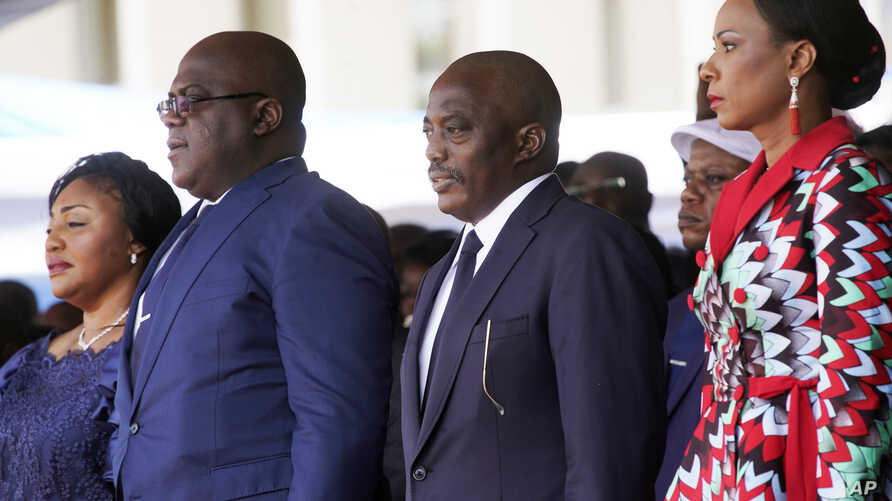 Congolese President Felix Tshisekedi, second left, his wife Denise Nyekeru, outgoing president Jospeh Kabila and his wife Olive Lembe di Sita , listen to the national anthem during the inauguration ceremony, in Kinshasa Thursday Jan. 24, 2019.