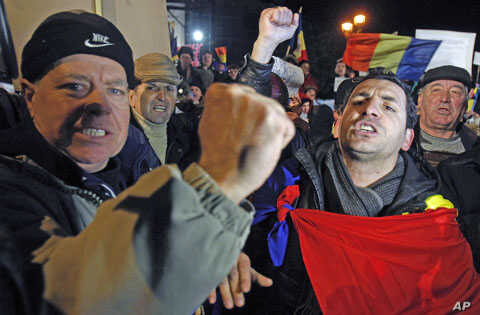 Demonstrators shout slogans during a protest against the government at the University Square in central Bucharest, Romania, January 23, 2012.