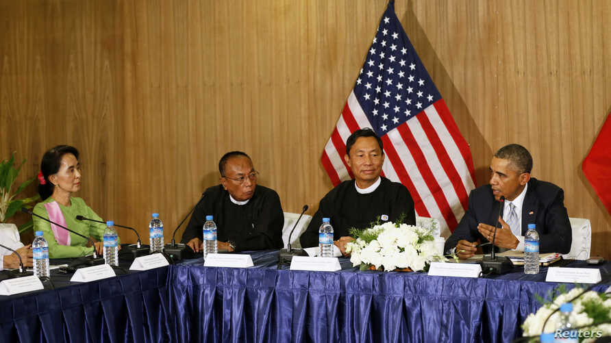 U.S. President Barack Obama speaks toward Myanmar opposition leader Aung San Suu Kyi (L) during a roundtable with members of parliament and civil society to discuss Myanmar's reform process in Naypyitaw, Nov. 13, 2014.