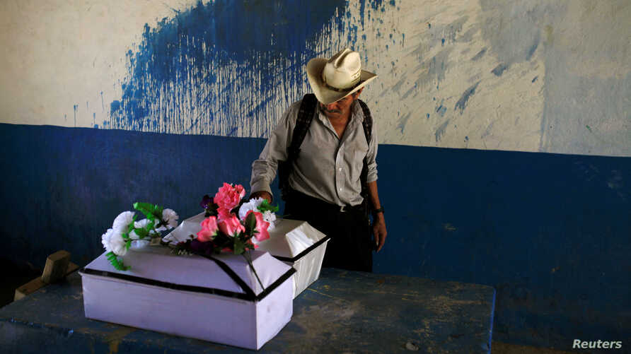 A man observes the remains of Petrona Chavarria and Vilma Ramos, who died in the El Mozote massacre, prior to their burial in the town of Jocoatique, El Salvador, Dec. 11, 2016.