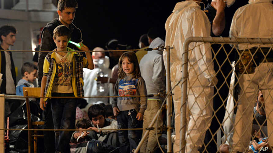 "FILE - Migrants wait to disembark from the Italian Navy Ship ""Grecale"" at Pozzallo harbour, Sicily, May 13, 2014."