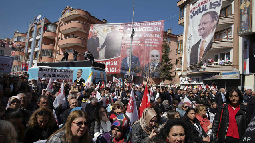 People listen to Mehmet Ozhaseki, the candidate of Turkey's ruling Justice and Development Party, AKP, and opposition Nationalist Movement Party, MHP, for Ankara Metropole, during a rally by MHP in Kecioren district, in Ankara, Turkey, Sunday, March