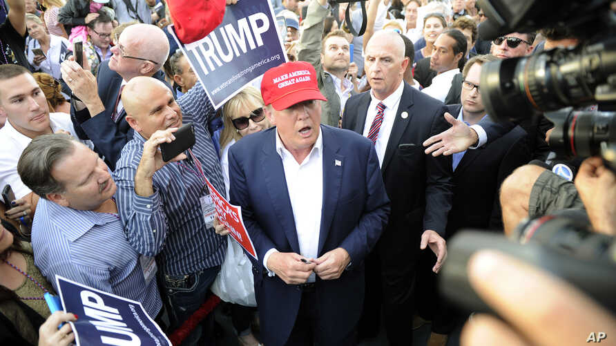 Republican presidential candidate Donald Trump, center, greets supporter after speaking at a campaign event aboard the USS Iowa battleship in Los Angeles, Sept. 15, 2015.