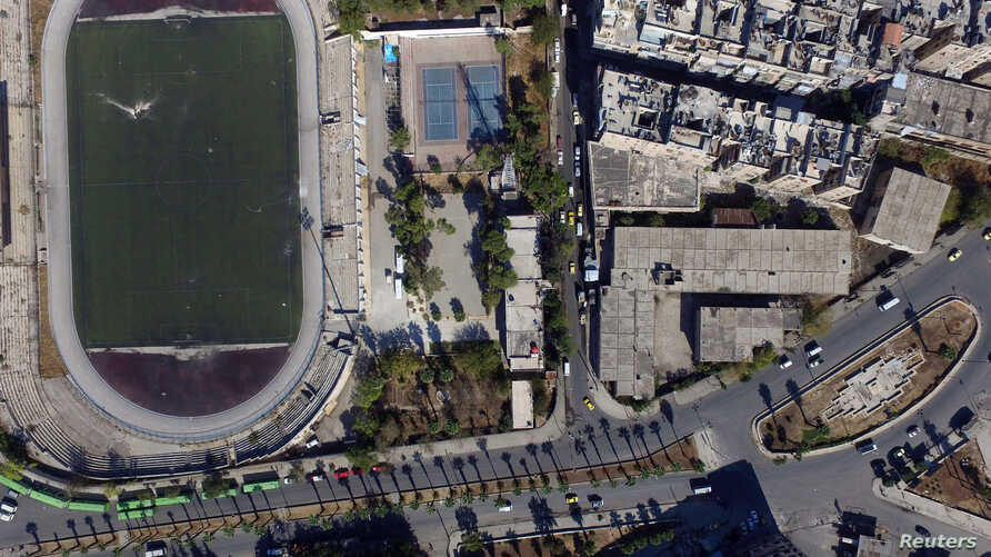 A general view taken with a drone shows buses parked outside the municipal stadium in the government-controlled area of Aleppo, as they wait to evacuate people wishing to leave besieged eastern Aleppo, Syria, Oct. 20, 2016.