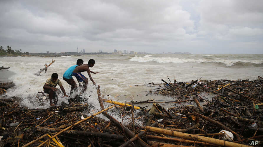 Sri Lankans look for recyclable material washed ashore with stormy waves in Colombo, Sri Lanka, May 21, 2018.