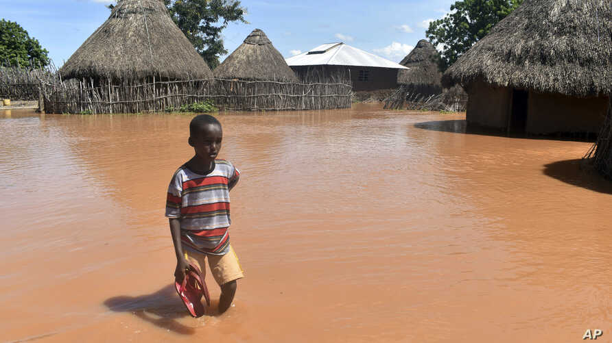 A boy stands outside his family home, which has been submerged by floods following prolonged heavy rains in Tana Delta, Coastal Kenya, April 27, 2018.