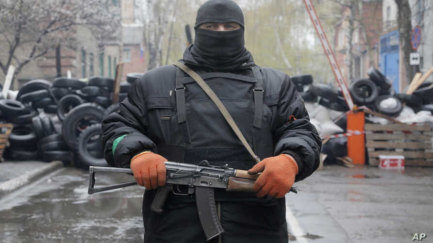 A pro-Russian gunman stands guard at a seized police station in the eastern Ukraine town of Slovyansk on Sunday, April 13, 2014. Pro-Moscow protesters have seized a number of government buildings in the east over the past week, undermining the author