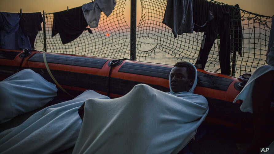 FILE - migrants rest on the deck of the Open Arms boat, after being rescued off the coast of Libya in the early hours of the night of Thursday, Aug. 2, 2018.