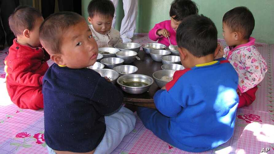 In this photo provided by the United Nation's World Food Program, a North Korean eat their lunch at a government run nursery in Pyongyang October 18, 2005.