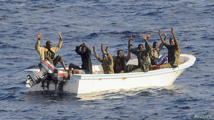Suspected pirates keep their hands in the air as directed by sailors aboard the guided-missile cruiser USS Vella Gulf (CG 72) (not shown), in the Gulf of Aden, February 11, 2009.