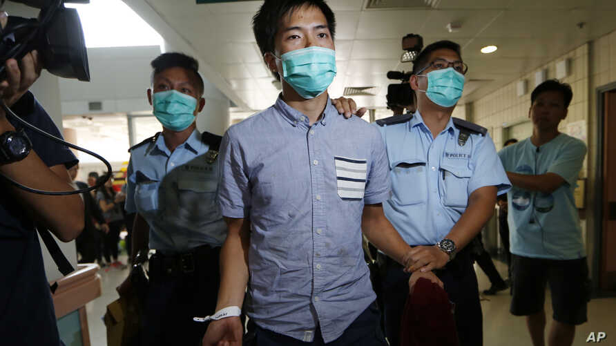 An Occupy Central protester, center, is escorted by police officers to a hospital for examine his injury during a clash between protesters and police in an occupied area near the government headquarters in Hong Kong, Wednesday, Oct. 15, 2014. Hong Ko