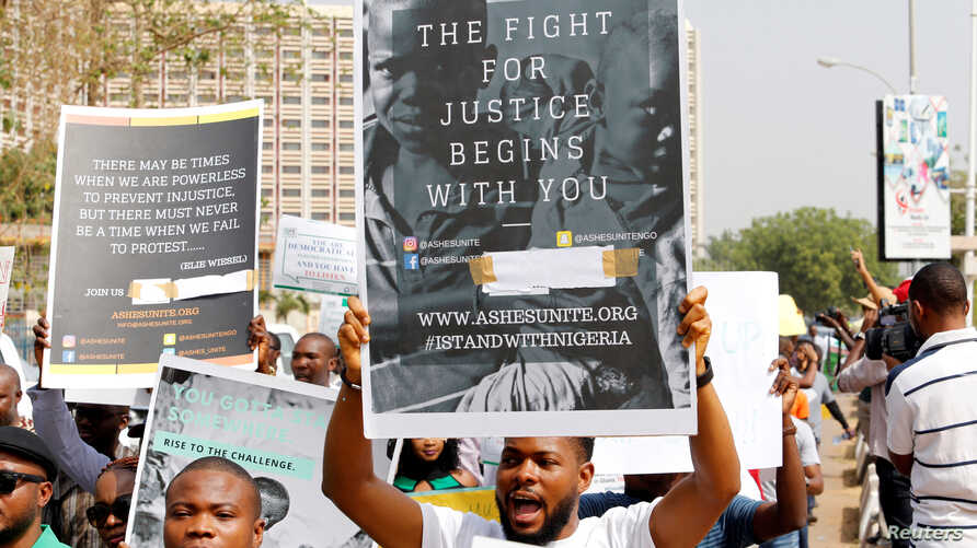 People hold signs as they take part in a protest march against Nigeria's President Muhammadu Buhari in Abuja, Nigeria, Feb. 6, 2017.