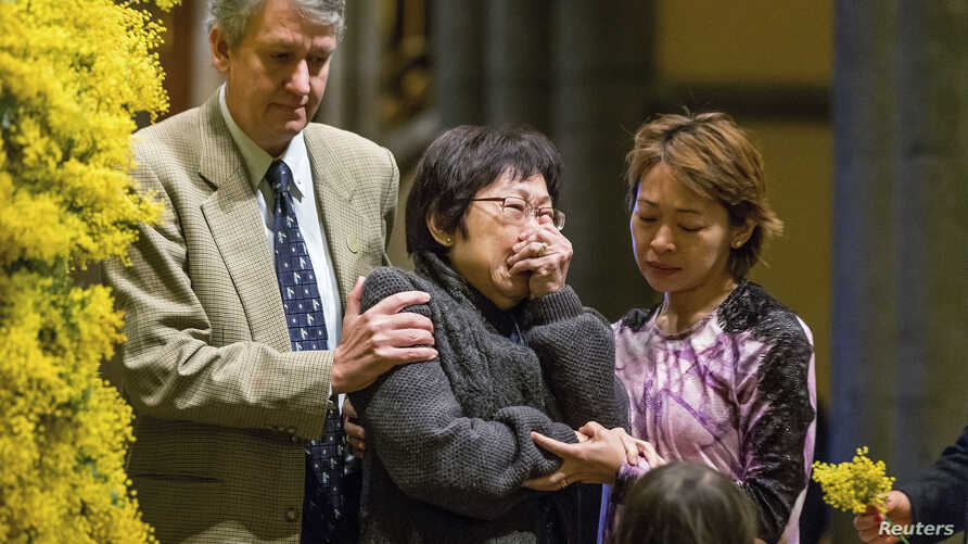 On Australia's national day of mourning for victims of downed Malaysia Airlines flight MH-17, a relative grieves during a service at St. Patrick's Cathedral in Melbourne Aug. 7, 2014.
