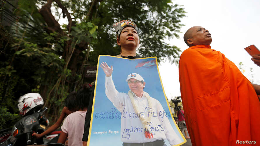 FILE - Supporters of Kem Sokha, opposition leader and ex-president of the now-dissolved Cambodia National Rescue Party (CNRP), hold up a poster near the Appeal Court in Phnom Penh, Cambodia, March 27, 2018.