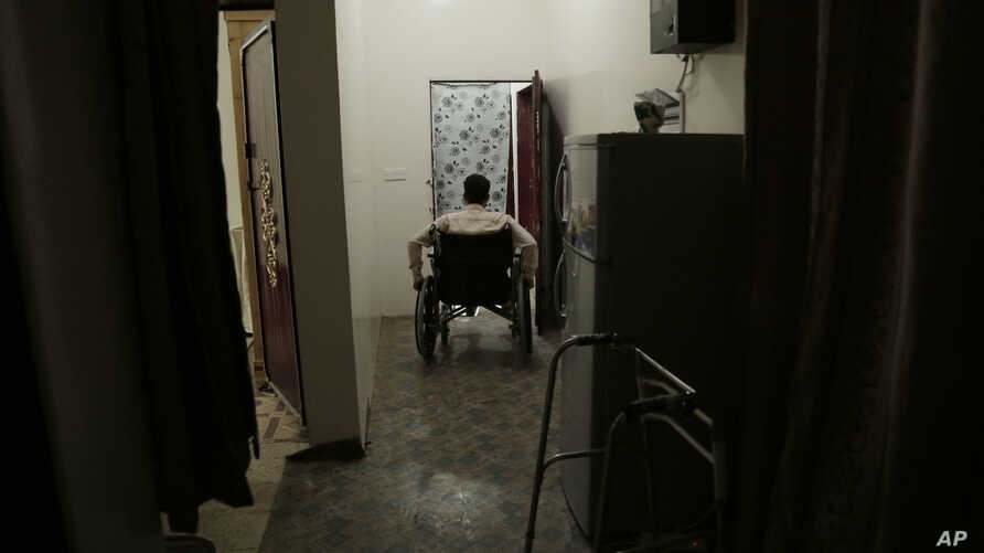 FILE - Anas al-Sarrari moves around in his wheelchair in his home in Marib, Yemen, July 29, 2018. He says he was hung by his wrists from the ceiling for 60 days and beaten while locked up in a prison run by Yemen's Houthi rebels.