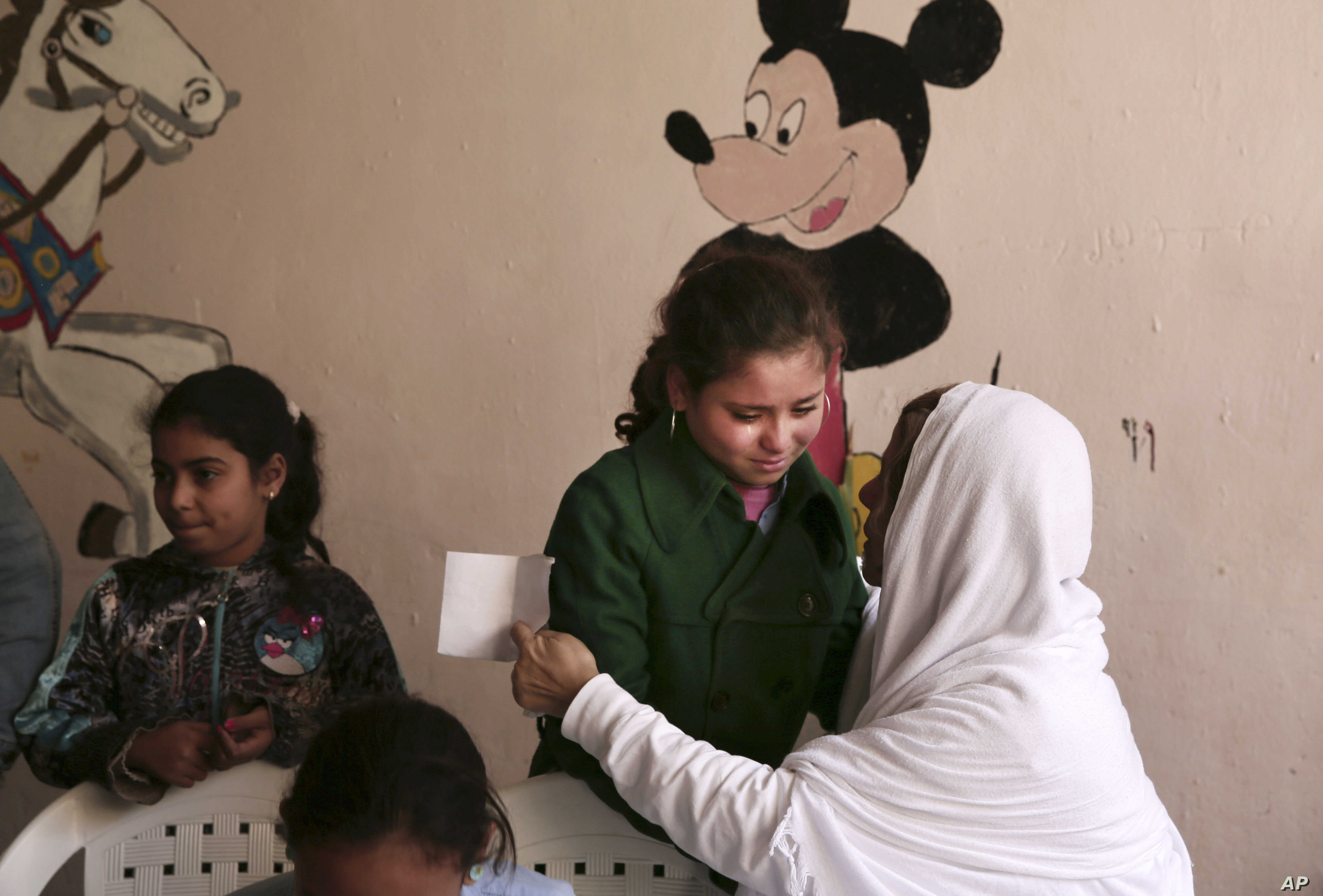 FILE - A woman comforts a child at a community development center in the Manshiet Nasr neighborhood of Cairo, Egypt, Feb. 25, 2015, as a Disney character is seen in the background.