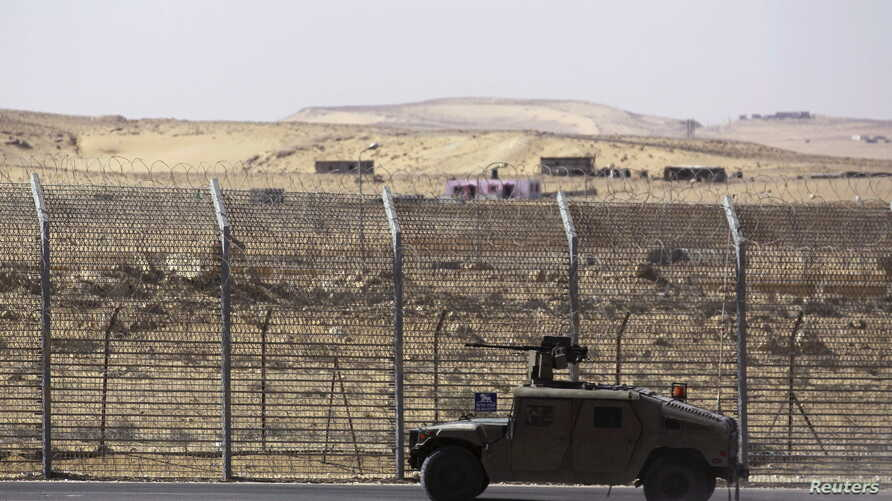 FILE - An armored Israeli military vehicle drives along Israel's border with Egypt's Sinai peninsula in  January 2014.