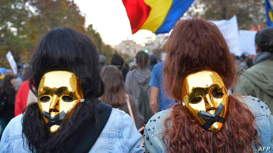 People wear golden masks during a protest in Bucharest. Thousands of people marched for the eighth consecutive Sunday in Romania against a Canadian gold mine plan to extract 300 tons of gold and 1,600 tons of silver over 16 years from Rosia Montana,