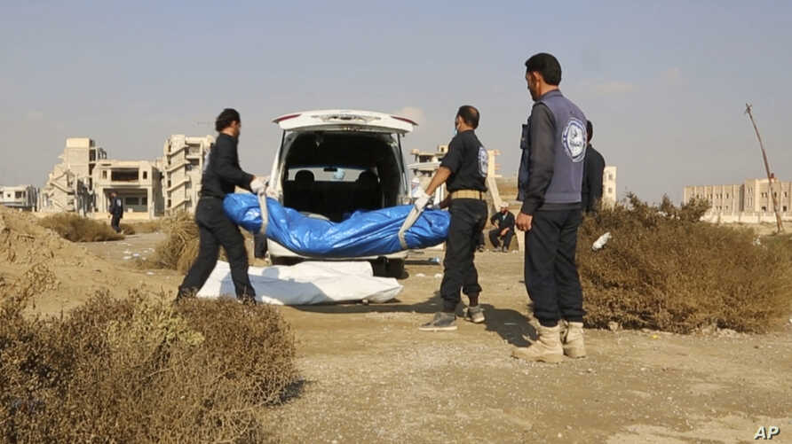 This frame grab from a video provided on Nov. 22, 2018, shows Syrian workers of a Raqqa group carrying human remains at the site of a mass grave believed to contain the bodies of civilians and Islamic State militants, in Raqqa.
