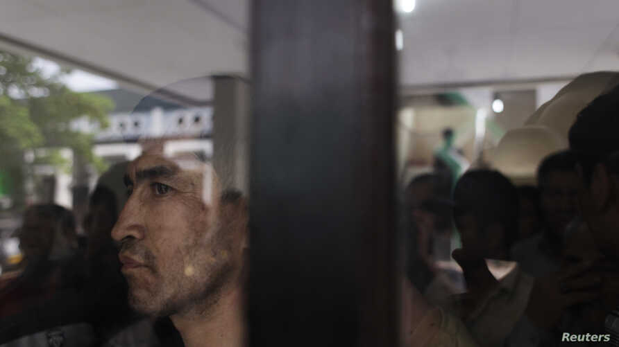 FILE - An ethnic Hazara man looks out from behind a glass panel at a temporary shelter in Karawang, Indonesia's West Java province.