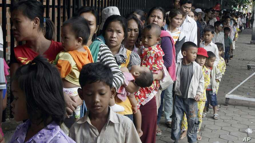 Cambodian villagers for countryside line up as wait for a medical check-up outside the children hospital of Kuntha Bopha, in Phnom Penh, Cambodia, Wednesday, July 11, 2012. A deadly form of a common childhood illness has been linked to many of the my