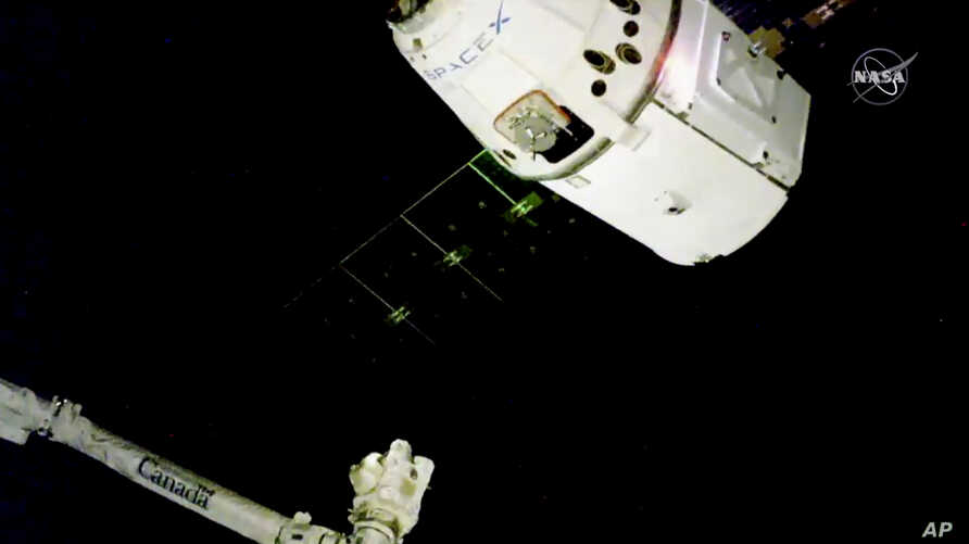 In this image taken from NASA Television, the SpaceX Dragon cargo spacecraft approaches the robotic arm for docking to the International Space Station, Saturday, Dec. 8, 2018.