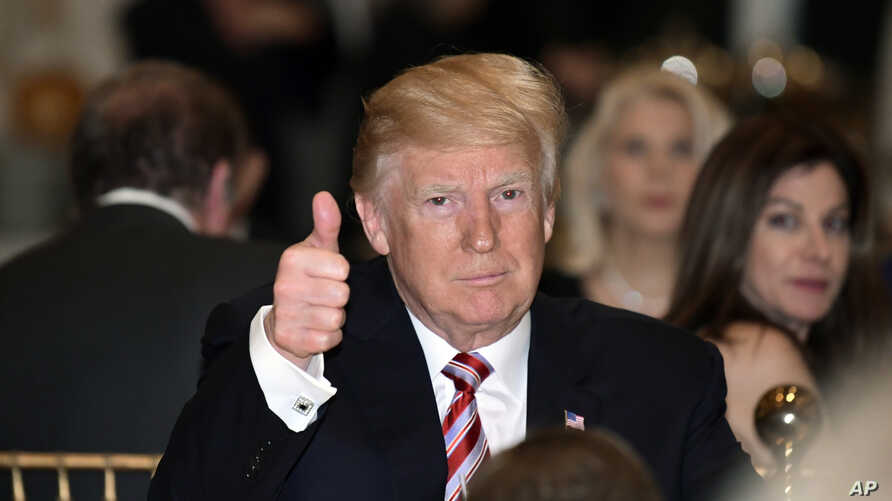 President Donald Trump gives a thumbs-up as he has Thanksgiving Day dinner at his Mar-a-Lago estate in Palm Beach, Fla., Thursday, Nov. 22, 2018.