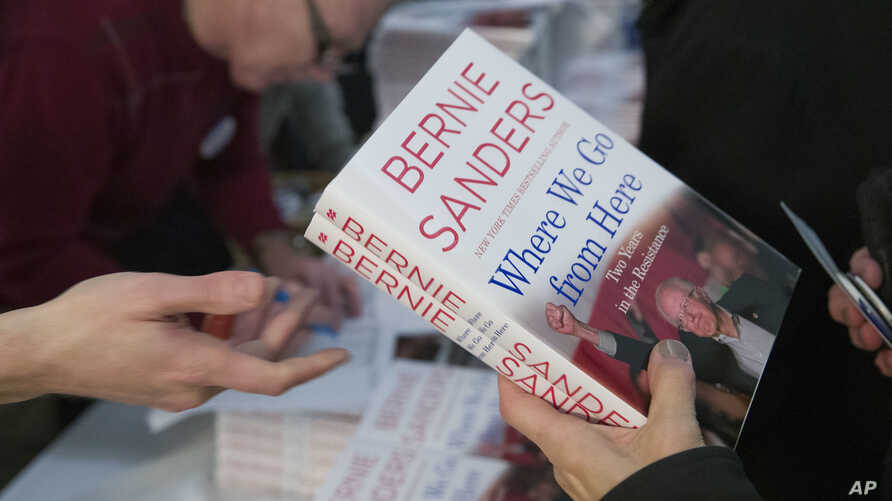 Attendees receive a copy of Sen. Bernie Sanders', I-Vt., new book, 'Where We Go From Here: Two Years in the Resistance', at a George Washington University/Politics and Prose event, Nov. 27, 2018, in Washington.