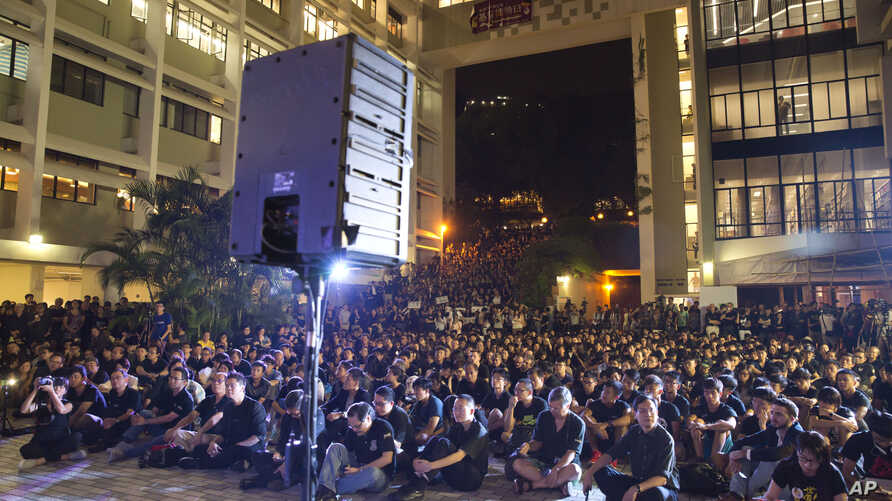 FILE - Hundreds of staff members and students from the University of Hong Kong,  in black, stage a demonstration on the campus in Hong Kong, Oct. 9, 2015.