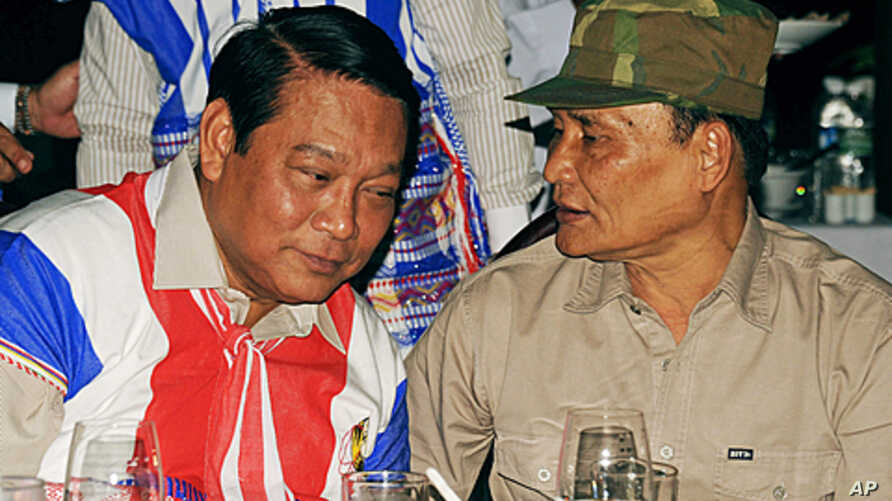 This picture shows a representative of the rebel Karen National Union (KNU) Saw Jawni (R) talking with Myanmar Immigration Minister Khin Yee (L) in Pa-An, Burma, January 11, 2012.