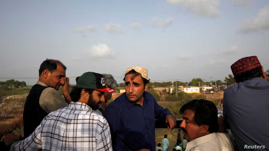 Bilawal Bhutto Zardari, chairman of the Pakistan People's Party (PPP), wearing a Sindhi topi hat, speaks to party workers on the roof of his bullet-proof bus, during a campaign rally ahead of general elections in District Thatta, Pakistan, July 2, 2