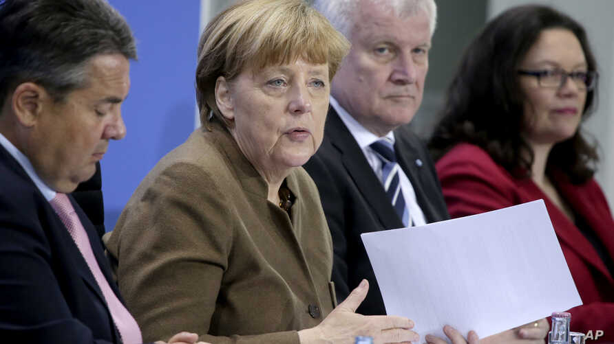 From left, Sigmar Gabriel, Chairman of the German Social Democrats, German Chancellor Angela Merkel, Horst Seehofer, Chairman of the German Christian Social Union and German Labor Minister Andrea Nahles address the media during a press conference in