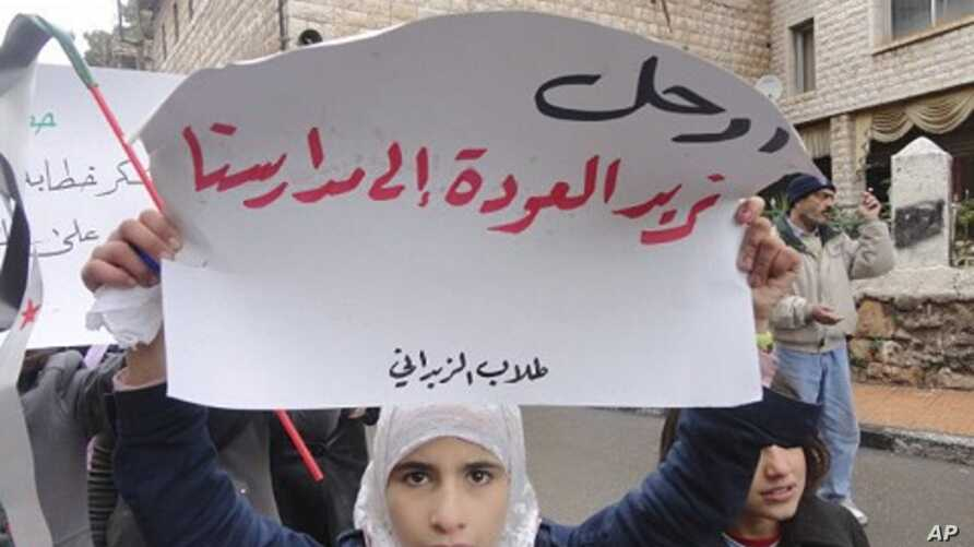 "Demonstrators protest against Syria's President Bashar al-Assad in Zabadani, near Damascus January 13, 2012. The placard reads, ""Go, we want to go back to our schools""."