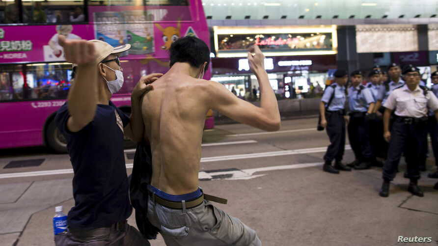 A pro-China demonstrator (L) hits a localist protester as police standing guard on the street look on during an anti-China protest at Mongkok shopping district in Hong Kong, China June 28, 2015. The police later broke up the fight, but did not detain
