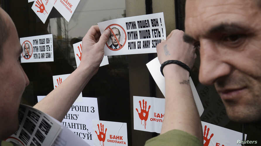 A member of a Ukrainian self-defense unit attaches stickers during a rally outside an office of Alfa bank in Kyiv, March 26, 2014.