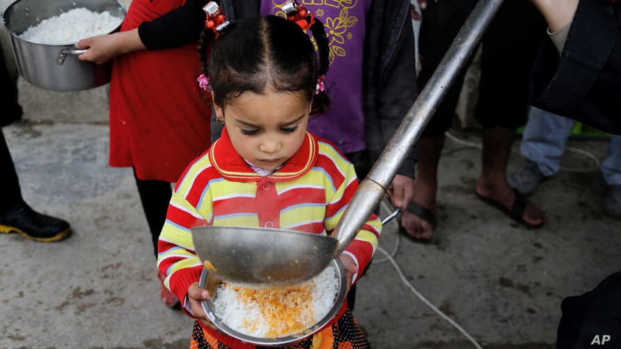 In this Jan. 23, 2016, photo, a displaced girl waits for donated food at al-Takia camp in Baghdad, Iraq. More than 3 million Iraqis are displaced within the country by violence and instability.