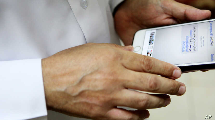 FILE - Human rights activist Ahmed Mansoor shows Associated Press journalists a screenshot of a spoof text message he received in Ajman, United Arab Emirates, Aug. 25, 2016. Mansoor was recently targeted by spyware that can hack into Apple's iPhone h