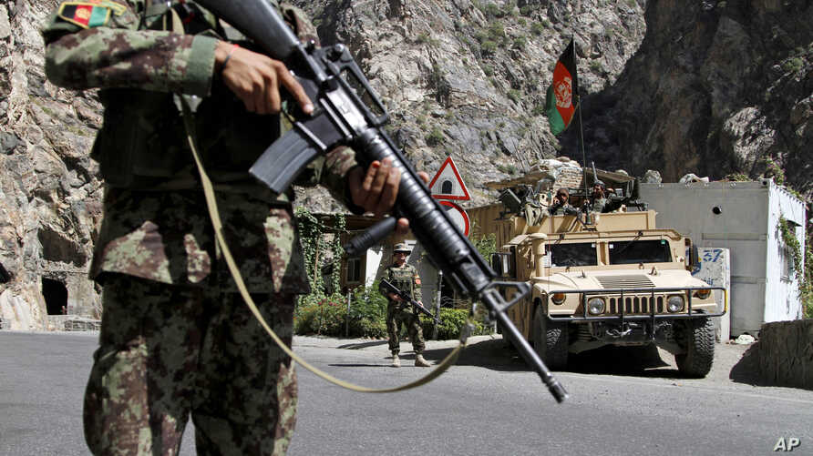 In this Tuesday, Aug. 27, 2013 photo, Afghan National Army soldiers stand guard on the outskirts of in Kabul, Afghanistan.