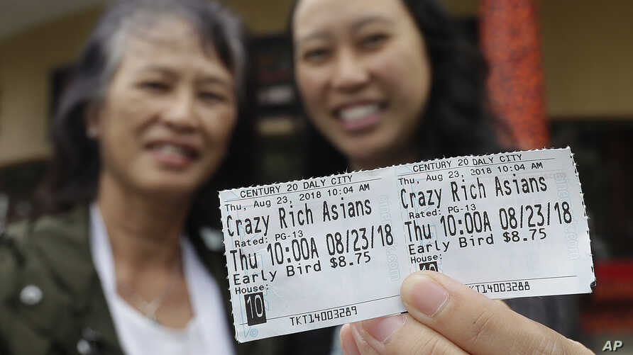 Audrey Sue-Matsumoto, right, holds tickets as she poses for photos with her mother Alice Sue while interviewed outside of a movie theater after watching the movie Crazy Rich Asians in Daly City, Calif.