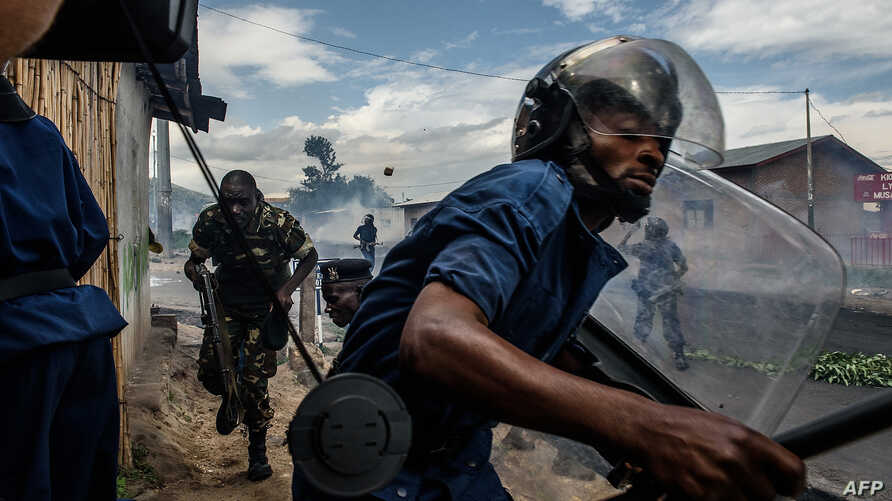 FILE - Burundi's policemen and army forces run after protesters against incumbent president Pierre Nkurunziza's bid for a 3rd term on 13 May 2015 in Bujumbura, May 13, 2015.